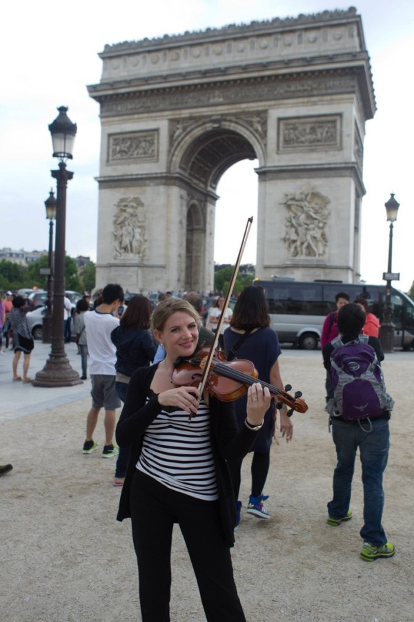 Ashley Rescot with violin at the Arc de Triomphe